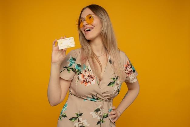 Portret van een mooie jonge vrouw die creditcard toont die over gele achtergrond wordt geïsoleerd