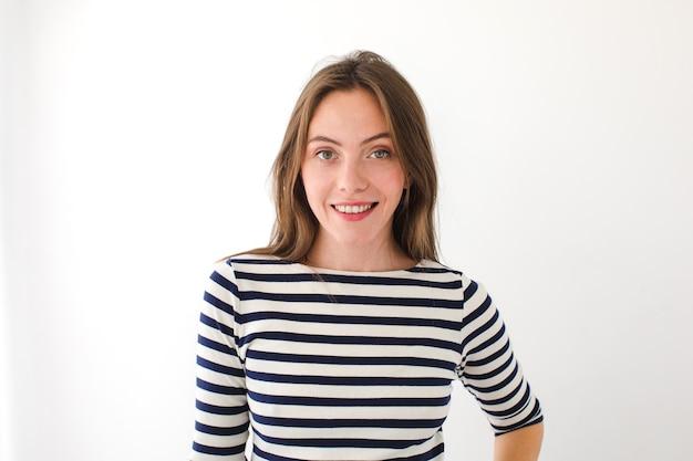 Portret van een mooie jonge vrouw die de camera bekijkt en glimlacht, geïsoleerd op een witte achtergrond