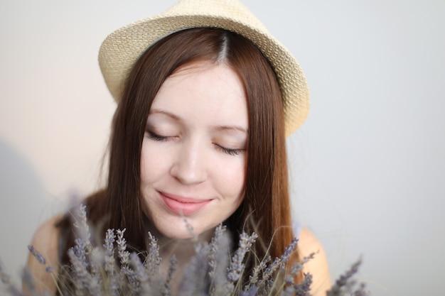 Portret van een mooie jonge vrouw die de zomerhoed draagt en lavendelbloemen houdt