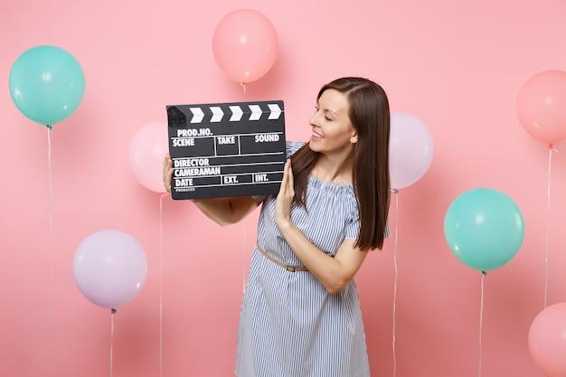 Portret van een mooie jonge vrouw die een blauwe jurk draagt en kijkt op klassieke zwarte film die filmklapper maakt op een pastelroze achtergrond met kleurrijke luchtballonnen. verjaardagsfeestje concept.