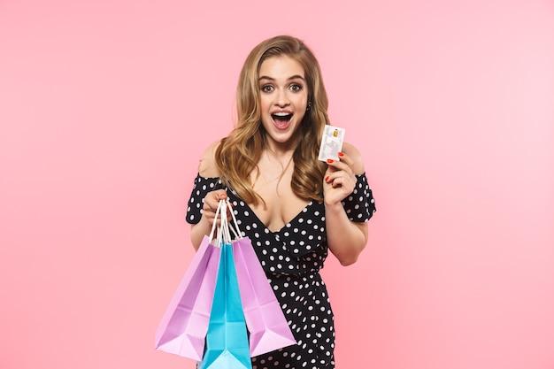 Portret van een mooie jonge vrouw die een jurk draagt die geïsoleerd over een roze muur staat, boodschappentassen draagt en een creditcard toont