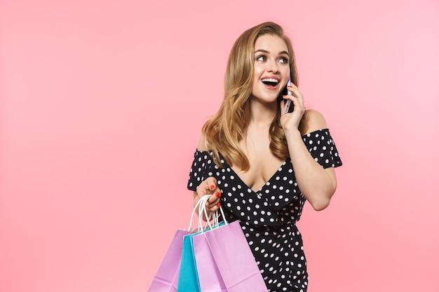 Portret van een mooie jonge vrouw die een jurk draagt die geïsoleerd over een roze muur staat, boodschappentassen draagt, mobiele telefoon gebruikt