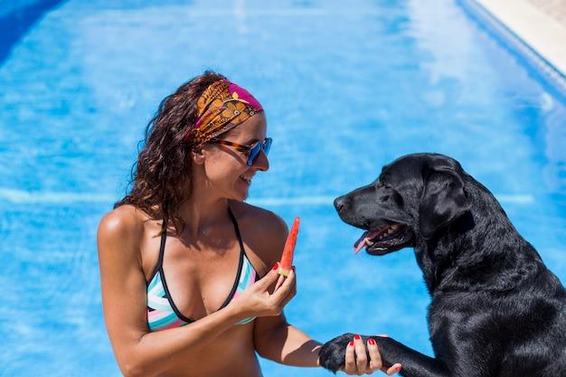 Portret van een mooie jonge vrouw die een stuk van watermeloen houdt en met haar zwart labrador glimlacht.
