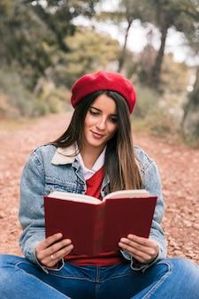 Portret van een mooie jonge vrouw die het boek in openlucht leest