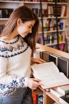 Portret van een mooie jonge vrouw die in een boekwinkel staat
