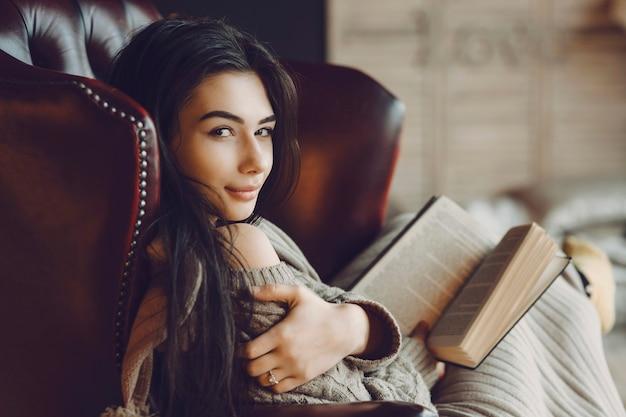 Portret van een mooie jonge vrouw die in een char zit en een boek leest bij een raam en over haar schouder in de camera kijkt.