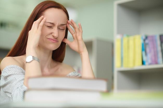 Portret van een mooie jonge vrouw die met haar ogen dicht aan de bibliotheekbalie zit tijdens de migraineaanval