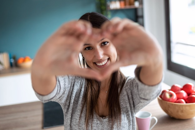 Portret van een mooie jonge vrouw die naar de camera kijkt terwijl ze hartvorm doet met haar handen in de keuken thuis.