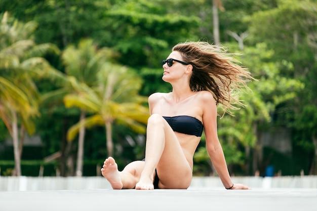 Portret van een mooie jonge vrouw die op de zee zonnebaadt