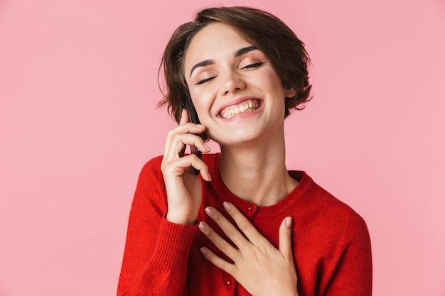 Portret van een mooie jonge vrouw die rode kleren draagt die zich geïsoleerd bevinden, die op mobiele telefoon spreken