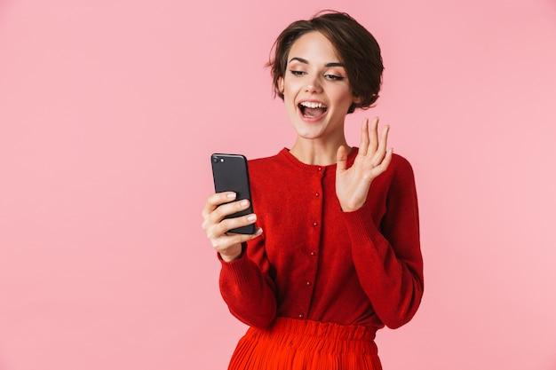 Portret van een mooie jonge vrouw die rode kleren draagt die zich geïsoleerd bevinden, die videogesprek hebben