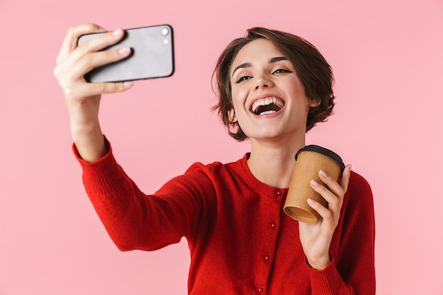 Portret van een mooie jonge vrouw die rode kleren draagt die zich geïsoleerd bevinden, een selfie nemen, afhaalmaaltijdenkoffie houden