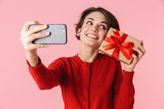 Portret van een mooie jonge vrouw die rode kleren draagt die zich geïsoleerd bevinden, een selfie nemen, die giftdoos houden