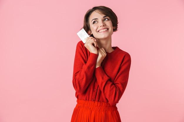 Portret van een mooie jonge vrouw die rode kleren draagt die zich geïsoleerd over roze achtergrond bevinden, creditcard houden