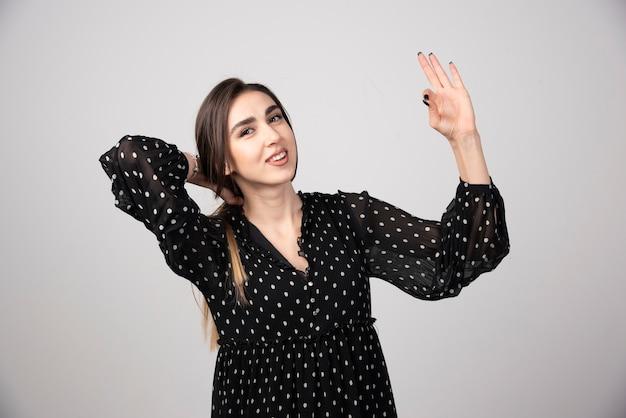 Portret van een mooie jonge vrouw die staat en een goed teken met vingers toont.