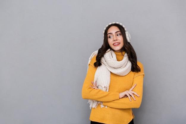 Portret van een mooie jonge vrouw die sweater en sjaal draagt die over grijze achtergrond wordt geïsoleerd, wegkijkend