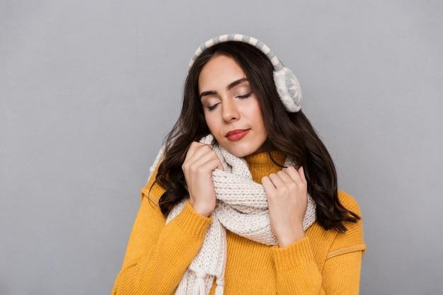 Portret van een mooie jonge vrouw die sweater en sjaal draagt die over grijze achtergrond wordt geïsoleerd
