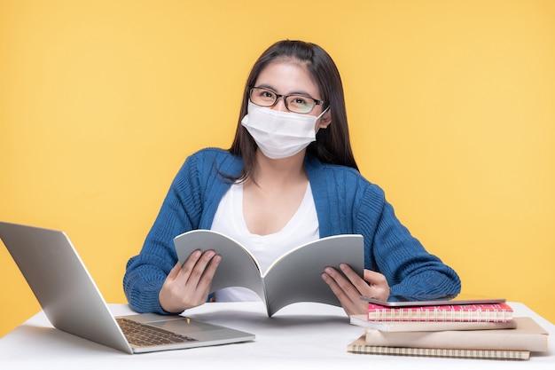 Portret van een mooie jonge vrouw die thuis met laptop en notitieboekje aan de tafel studeert - online e-learning systeem bestuderen