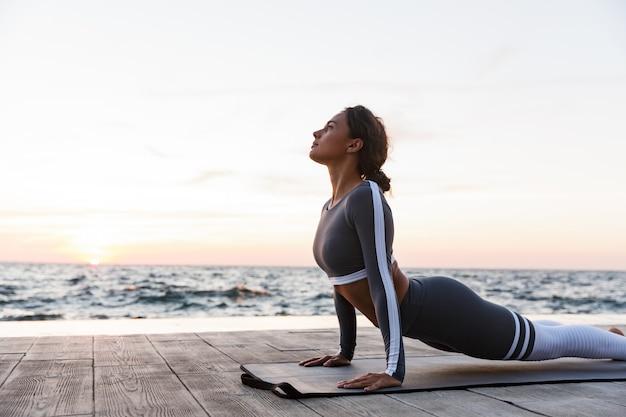 Portret van een mooie jonge vrouw die yogaoefeningen doet