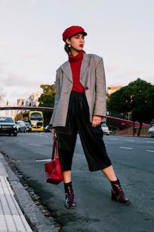 Portret van een mooie jonge vrouw die zich op weg met zak bevindt
