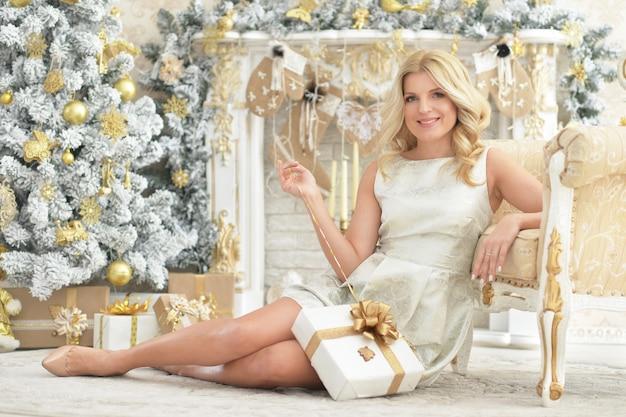 Portret van een mooie jonge vrouw die zich voordeed in een kamer die is ingericht voor kerstvakantie