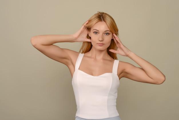 Portret van een mooie jonge vrouw die zich voordeed in een witte blouse in de studio