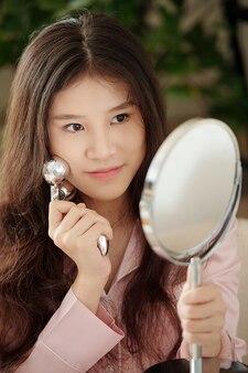 Portret van een mooie jonge vrouw die zichzelf een lymfedrainagemassage geeft met behulp van een metalen roller