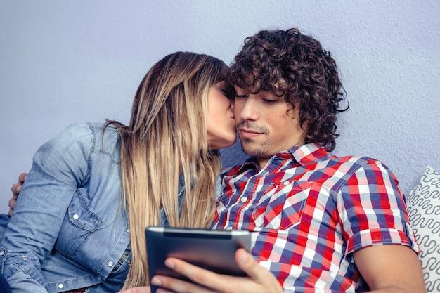 Portret van een mooie jonge vrouw die zoent met een knappe man terwijl hij er uitziet als een elektronische tablet. liefde en vrije tijd concept.