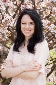 Portret van een mooie jonge vrouw door roze kers