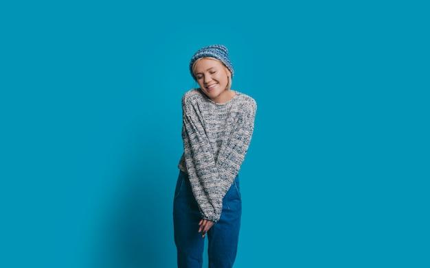 Portret van een mooie jonge vrouw gekleed in blauw lachend met gesloten ogen gelukkig geïsoleerd op blauwe studio muur.