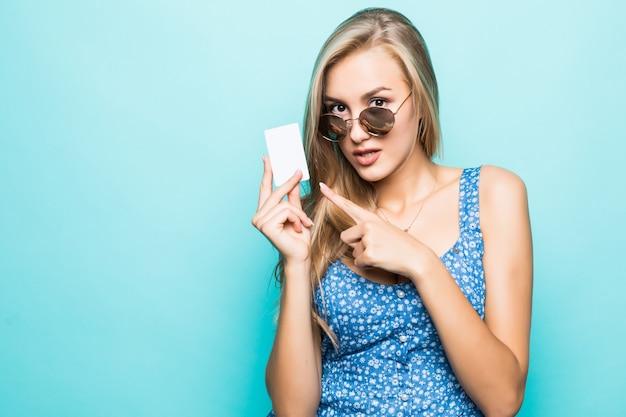 Portret van een mooie jonge vrouw gekleed in trui wijzende vinger op creditcard geïsoleerd op blauwe achtergrond