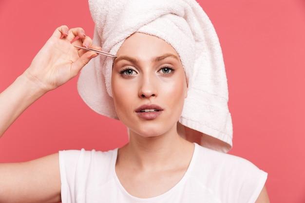 Portret van een mooie jonge vrouw gewikkeld in een witte handdoek na het douchen die haar wenkbrauwen plukt met een pincet geïsoleerd over roze muur