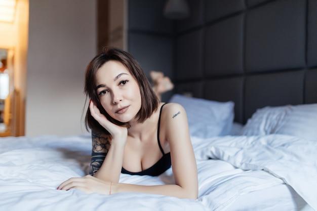 Portret van een mooie jonge vrouw in bed in de vroege ochtend