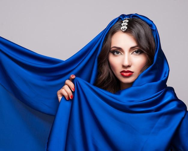 Portret van een mooie jonge vrouw in blauwe stof