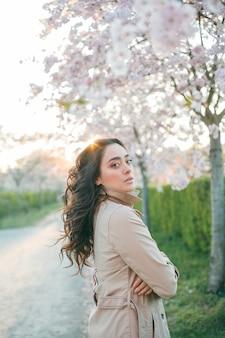 Portret van een mooie jonge vrouw in bloeiende sakura bij zonsondergang
