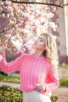 Portret van een mooie jonge vrouw in de buurt van een magnolia. voorjaar.