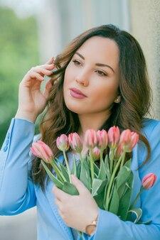 Portret van een mooie jonge vrouw in een blauw pak met een boeket tulpen