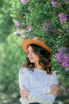 Portret van een mooie jonge vrouw in een bloeiende lila park.