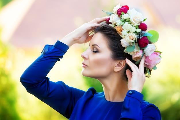 Portret van een mooie jonge vrouw in een krans van rozen, buiten in de bloemrijke tuin.