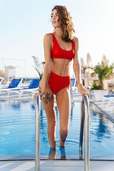 Portret van een mooie jonge vrouw in een rood zwempak die opzij kijkt en uit het zwembad komt op het luxe strand