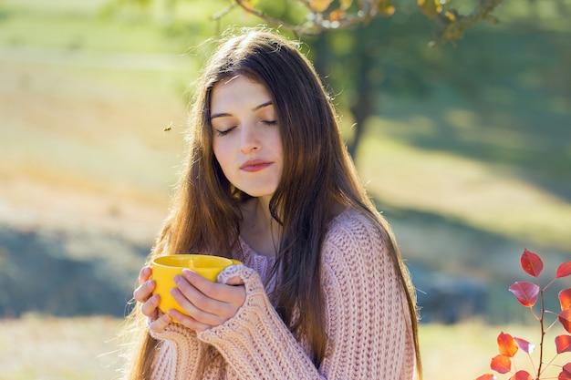 Portret van een mooie jonge vrouw in een stijlvolle gebreide trui die op het gouden herfstbos staat