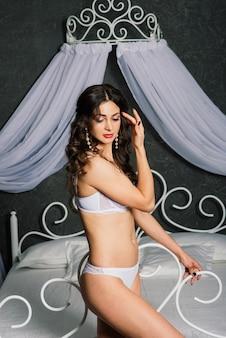 Portret van een mooie jonge vrouw in een wit ondergoed. ochtend van de bruid.