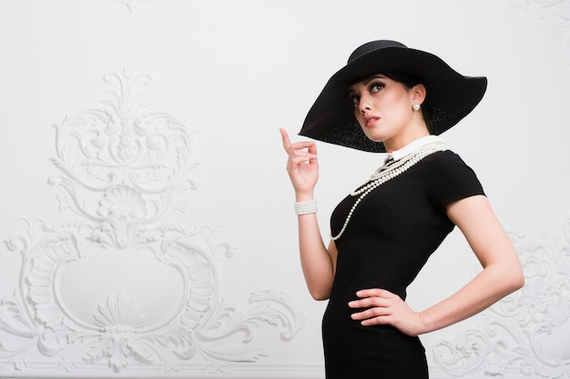 Portret van een mooie jonge vrouw in retro stijl in een elegante zwarte hoed en jurk op luxe rococco muur achtergrond