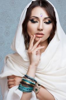 Portret van een mooie jonge vrouw in witte stof