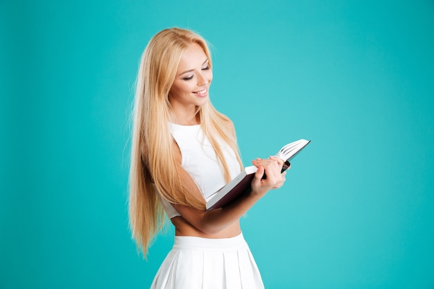 Portret van een mooie jonge vrouw leesboek geïsoleerd op de blauwe achtergrond