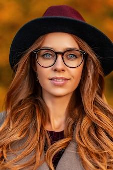 Portret van een mooie jonge vrouw met blauwe ogen met bruin haar met natuurlijke make-up in een elegante hoed in een stijlvolle bril in een trendy jas. europees hipster meisje buiten in het park. herfst look.