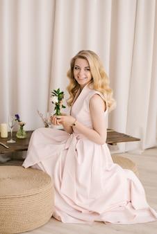 Portret van een mooie jonge vrouw met blond krullend haar in een delicate jurk