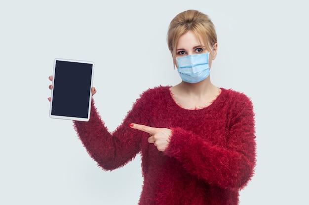 Portret van een mooie jonge vrouw met een chirurgisch medisch masker in een rode blouse die staat en het lege scherm van de tablet vasthoudt en met de vinger naar het apparaat wijst en naar de camera kijkt. binnen, geïsoleerd, studio-opname