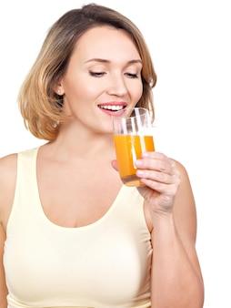 Portret van een mooie jonge vrouw met een glas jus d'orange - dat op wit wordt geïsoleerd.