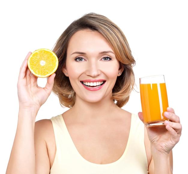 Portret van een mooie jonge vrouw met een glas sap en sinaasappel - dat op wit wordt geïsoleerd.